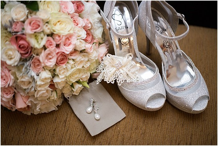 A wedding still life of flowers, earrings and shoes - wedding flash photography
