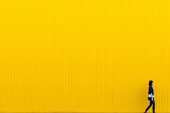 colorful portrait of a female model walking passed a bright yellow wall - using vibrant colors in photography