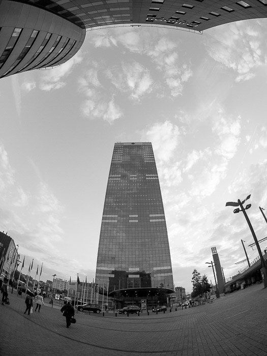 A tall skyscraper shot in black and white with a fisheye lens