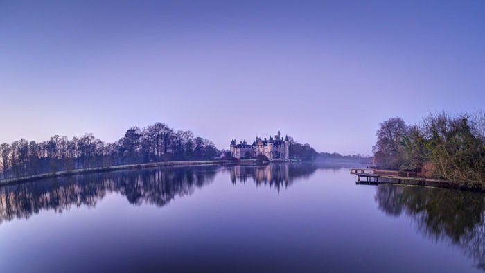 Beautiful panorama of a castle in the background of a peaceful lake