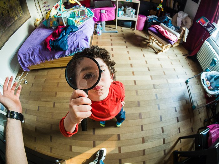 A typical funny fisheye portrait of a little boy holding a magnifying glass towards the camera