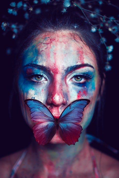 Woman with painted face and a butterfly on her mouth