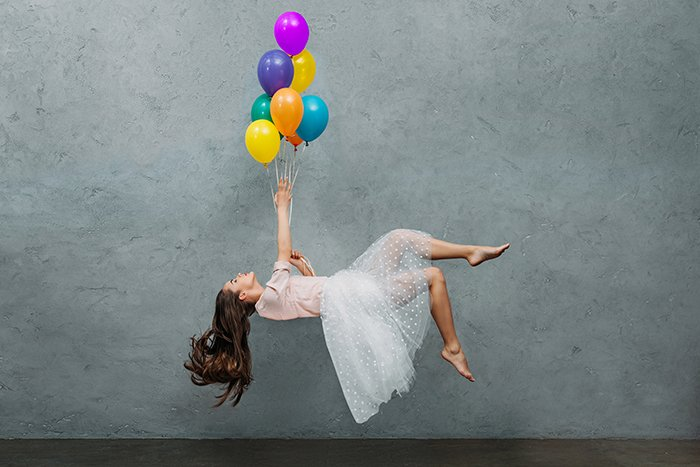 Young woman levitating with ballons.