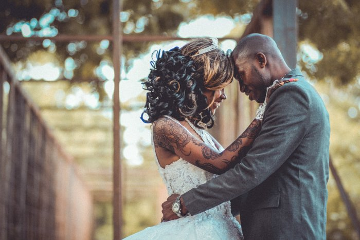 Artistic portrait of a newlywed couple embracing outdoors - fine art wedding photography
