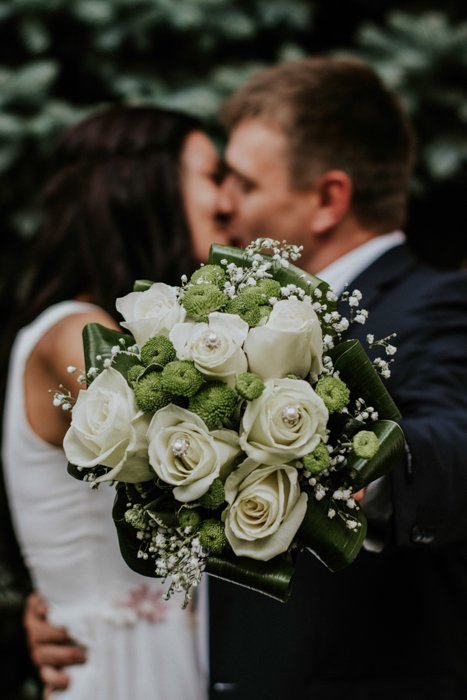 Artistic portrait of a newlywed couple holding a bouquet of flowers towards the camera - fine art wedding photography