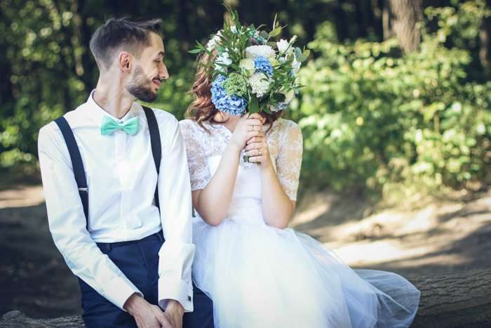 A fine art wedding photography shot of a couple posing humorously outdoors
