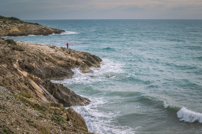 A beautiful coastal landscape with focus on a man in red jacket