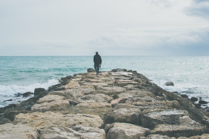 bright and airy shot of a man walking towards the sea on a rocky pier - focal point photography