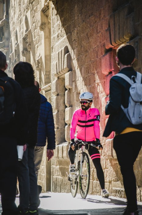 Street view of people with focus on a biker in a pink jacket