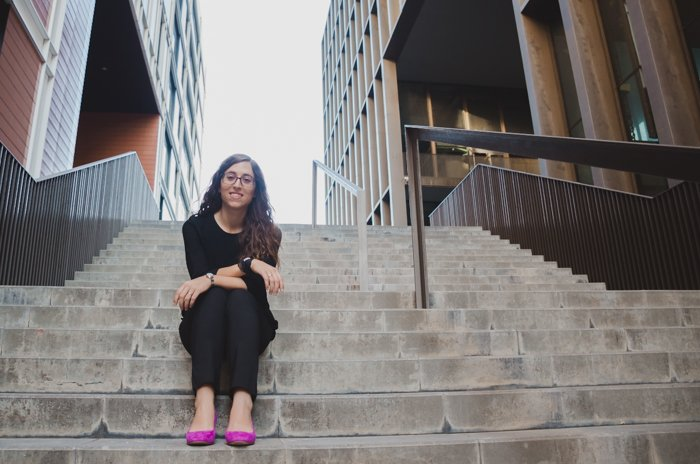 A female model in pink shoes sitting on stone steps