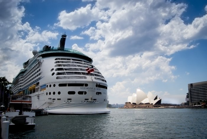 A large ferry docked at a harbor with the Sydney opera house behind