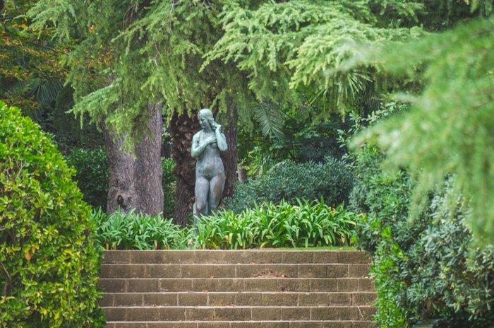 A bronze statue of a woman in a garden