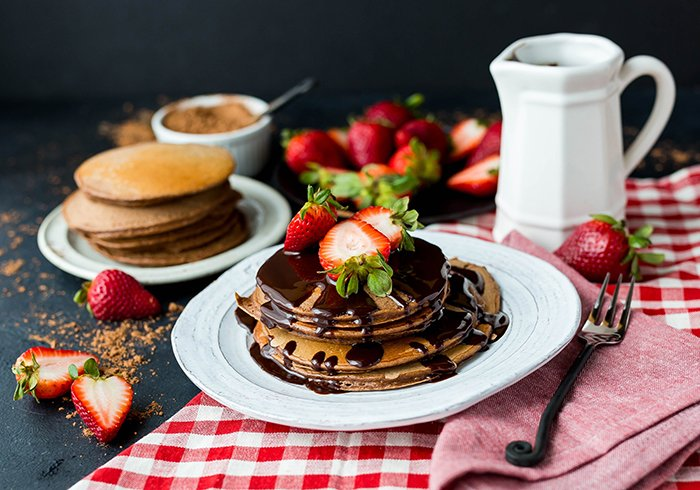 A stunning still life of a plate of chocolate covered pancakes shot using ring light photography