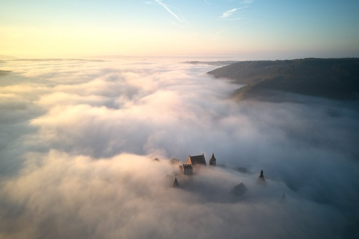 aerial photo of a castle submerged in mist - beautiful photography principles