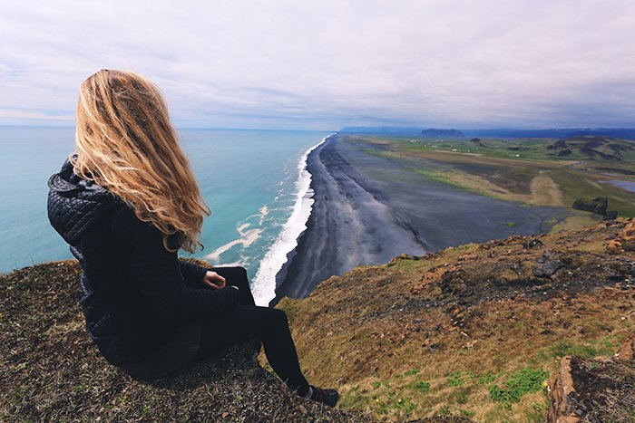 a woman sitting on a cliff overlooking a beautiful coastal landscape - beautiful photography principles