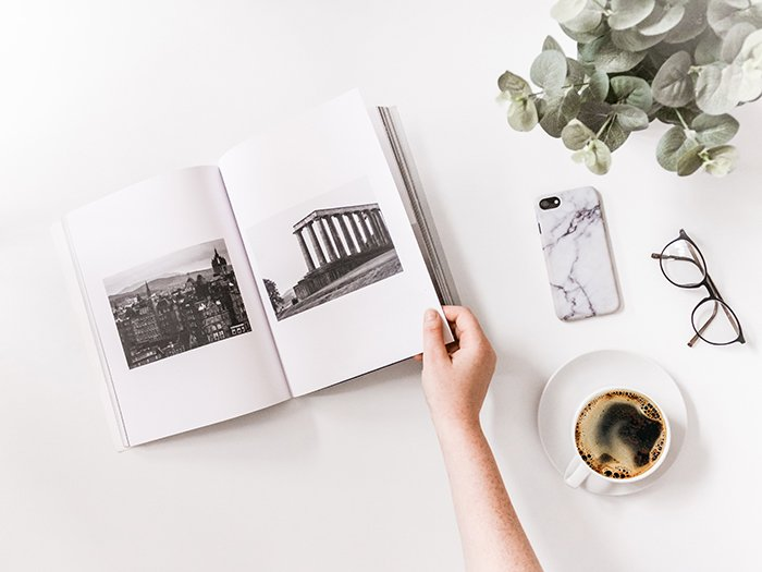 An artistic flatlay of a cool photobook, a coffee cup, glasses and a smartphone on a white table - how to make your own photo book to make your own photo book