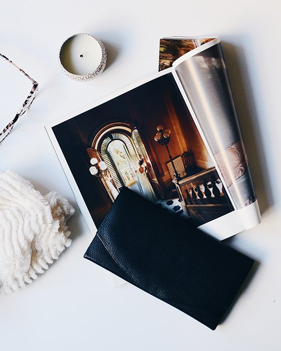 An artistic flatlay of a full-page photobook, a candle, glasses and a wallet on a white table - how to make your own photo book to make your own photo book