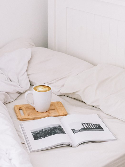 An artistic still life of a photobook and a cup of coffee on a bed - how to make your own photo book to make your own photo book