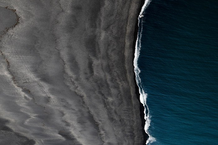 Aerial landscape photo of the sea coming into a beach - using color theory in landscape photos