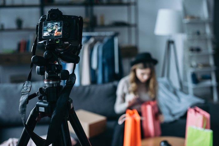 A DSLR camera set up on a tripod to take a portrait of a female model