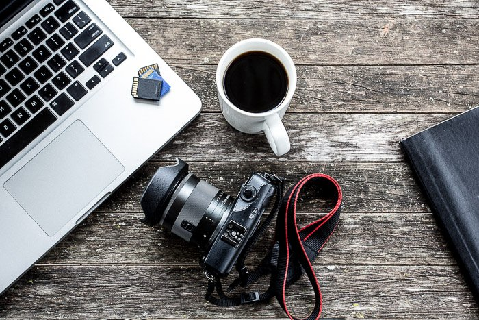 Flat lay of a photographers desk featuring laptop, DSLR camera, coffee cup