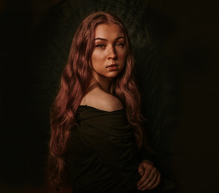 Atmospheric portrait of a moody female model posing against a black background - examples of dark portraits