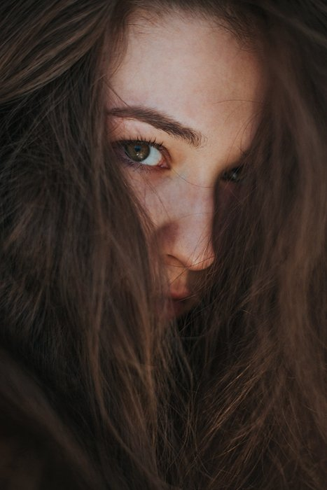 Atmospheric close up portrait of a moody female model with hair covering her face - examples of dark portraits
