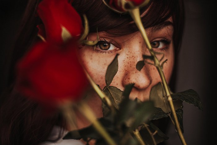 Atmospheric close up portrait of a moody female model with roses covering her face - examples of dark portraits