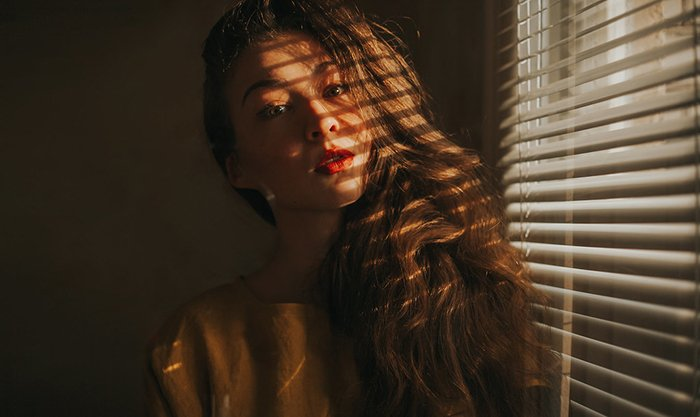A moody portrait of a female model posed by a window, shadows of the window blinds cast on her face and hair - examples of dark portraits
