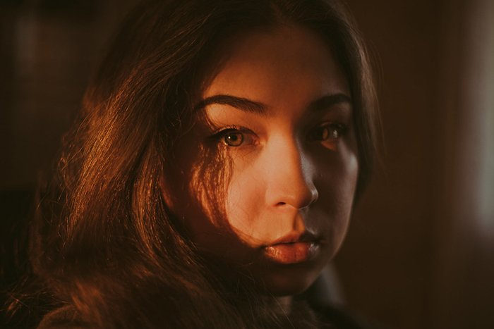 Atmospheric portrait of a moody female model looking straight to the camera in low light - examples of dark portraits