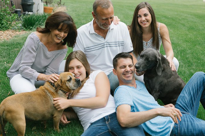 A family of five posing casually outdoors with dogs - the decisive moment in photography