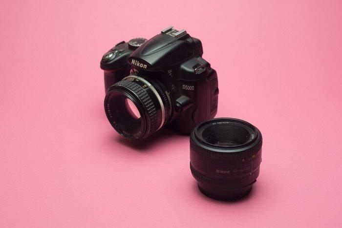 A Nikon DSLR lens on baby pink background