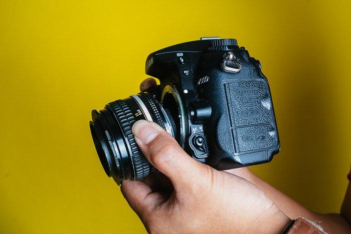 A Nikon DSLR lens on yellow background
