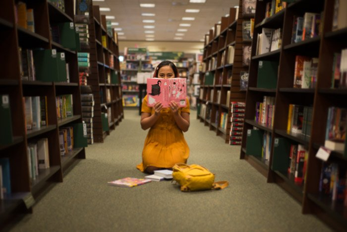 Conceptual portrait of a girl reading on a library floor shot using freelensing photography