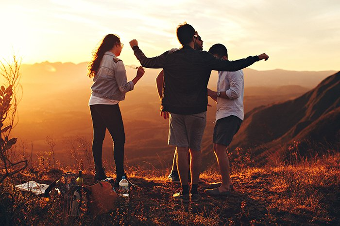 A candid outdoor portrait of a group of friends chatting outdoors at sunset - bff pictures