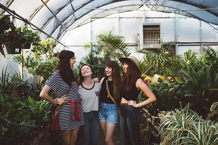 A candid portrait of a group of female friends chatting in a greenhouse - friendship images