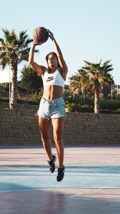 a portrait of a female basketball player jumping with the ball - basketball photoshoot