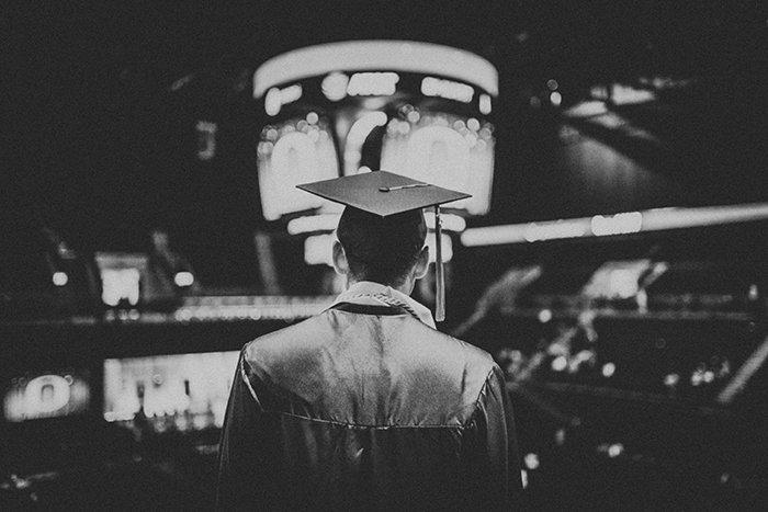 Candid monotone graduation portrait of a male student indoors