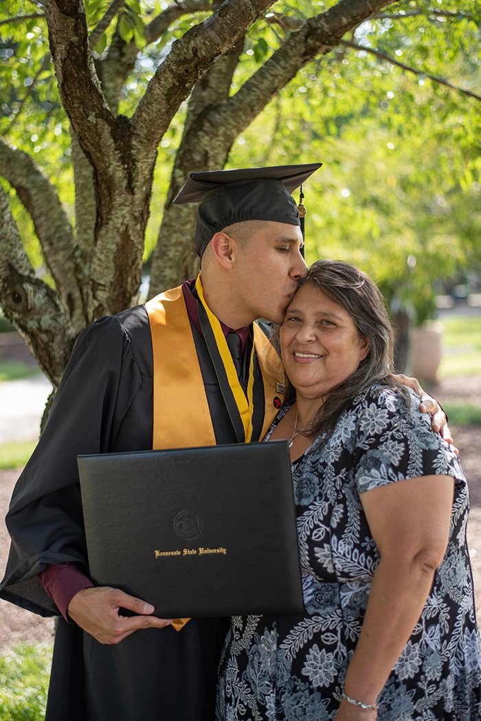 Beautiful graduation portrait of a male student embracing his mother outdoors