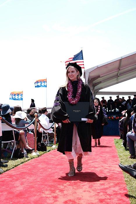 Beautiful candid graduation portrait of a female student walking outdoors