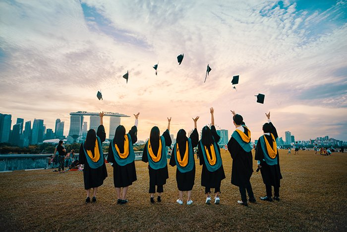 A group of graduation students tossing their hats in the air - graduation photography