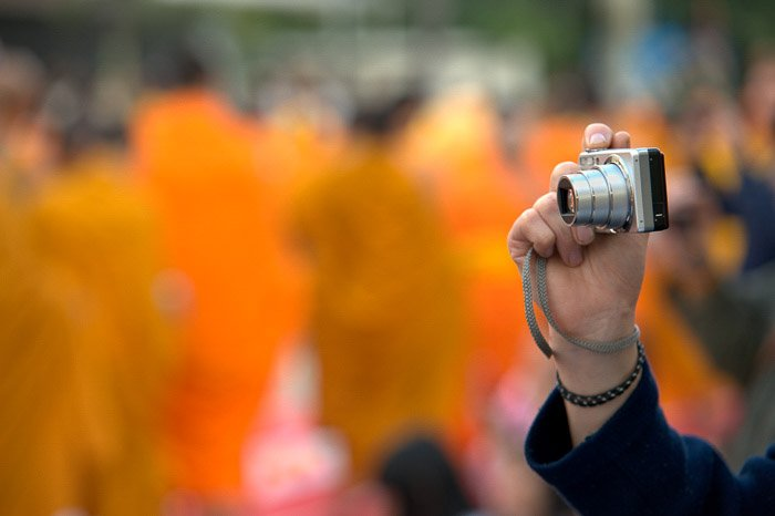 A person holding a compact camera against a blurry background - grey market cameras
