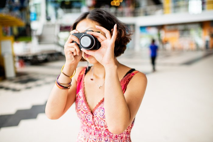 A female photographer holding a compact camera against a blurry background - grey market cameras