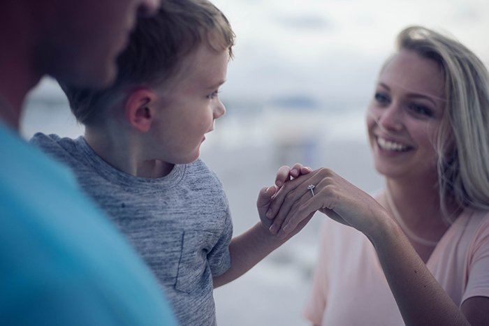 A candid shot of a father holding a young boy towards his smiling mother - lifestyle portraits