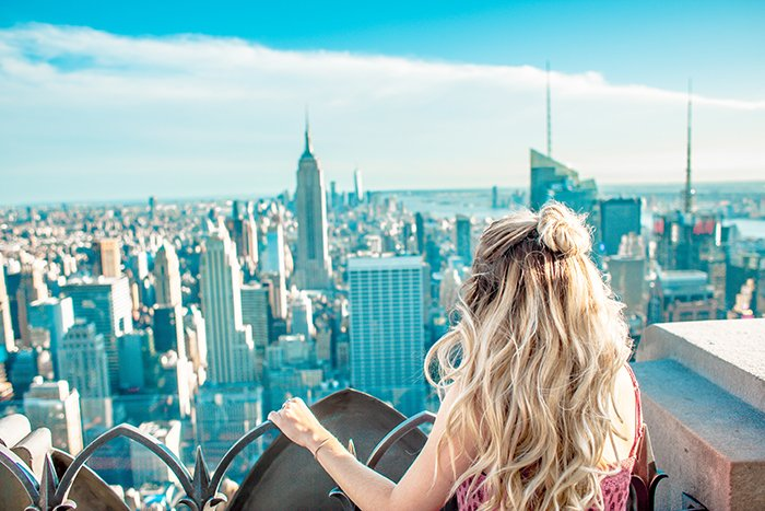 A blonde model posing on a rooftop gazing out at a sprawling cityscape - lifestyle portraits