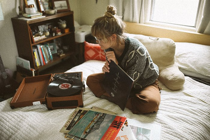 An analog photography portrait of a girl sitting on her bed choosing vinyl records to play in a cozy room - lifestyle portraits