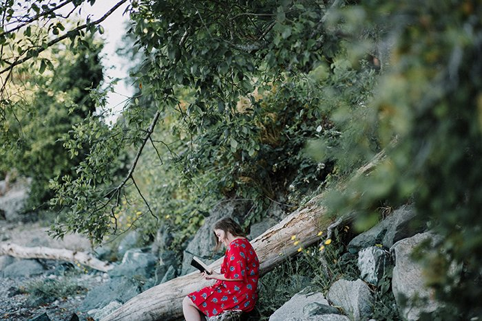 A female model reading a book under a tree - lifestyle portraits
