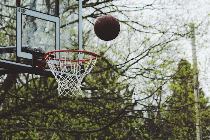 A basketball being thrown into a net - sports photography tips