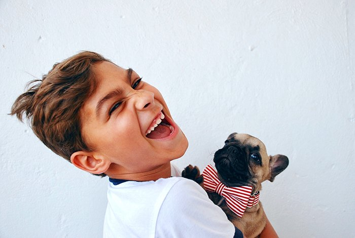 Fun portrait of a laughing young boy holding a small dog - smiling people