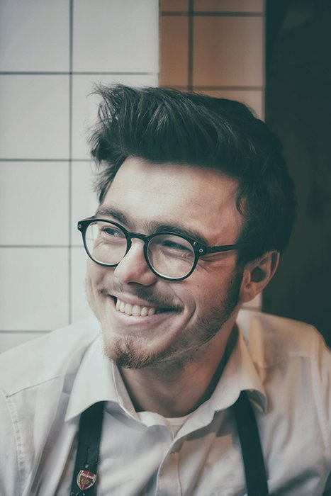 A portrait of a man in glasses smiling natural